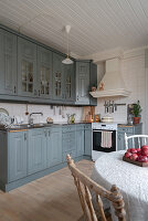Grey cupboards in rustic kitchen-dining room in country-house style
