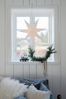 Paper star and minimalist Christmas wreath in window