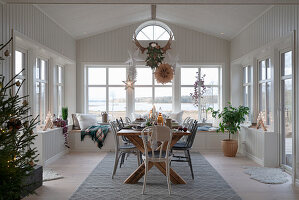 Set table in Scandinavian-style conservatory decorated for Christmas