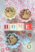 The word 'Home' on paper cubes and cat-shaped biscuits in dishes
