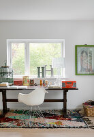 Designer chair at old wooden table with vintage accessories below window