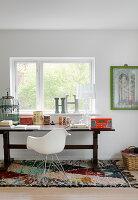 Designerstuhl am alten Holztisch mit Vintagedeko vorm Fenster