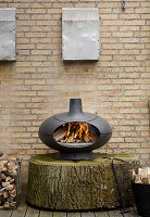 Modern pizza oven on large slice of tree trunk against brick wall