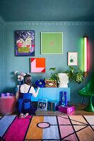 Frau kniet vorm Sideboard im kitschig bunten Wohnzimmer