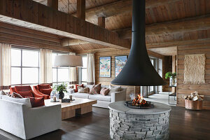 Open fireplace in living room of elegant log cabin