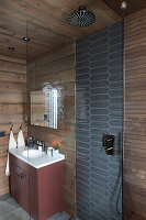 Shower and sink in rustic bathroom with wood-clad walls