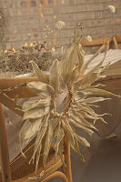 Wreath of maize leaves on chair at rustically set table