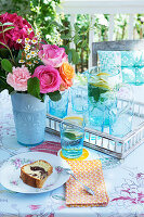 Summery bouquet, lemonade and cake on table