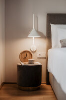 Illuminated bedside table and wall-mounted lamp next to bed with white bed linen