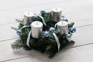 Handmade Advent wreath with silver candles and blue Christmas-tree baubles