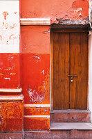 Wooden door in red wall with peeling paint