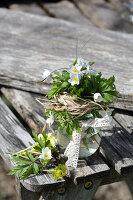 Kleiner Strauß aus Buschwindröschen mit Grasmanschette und Spitzenband