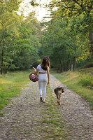 Frau mit Hund beim Waldspaziergang