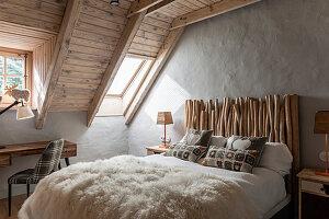 Gästezimmer im skandinavischen Stil, Doppelbett mit Ästen als Betthaupt