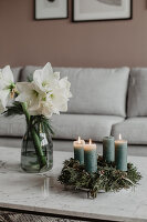 Advent wreath with green candles and white amaryllis in glass vase
