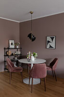 Velvet-covered chairs around round table in dining room in earthy shades