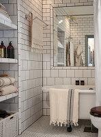 White tiles and bathtub below large mirror in bathroom