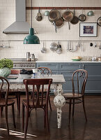 Pans hanging from rack above kitchen counter with grey cabinets and antique table in dining area