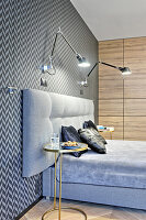 Anglepoise lamps on wall above bed and wallpaper with graphic pattern