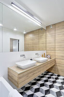 Floor with graphic pattern in bathroom with mirrored wall