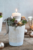 Wintry arrangement of candle and dried flowers in flower pot