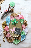 Golden tin lid surrounded by frame made from paper fans
