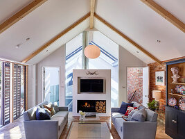 Grey sofas and modern open fireplace in living room below pitched roof
