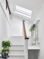 Steps leading to white, free-standing bathtub on landing below sloping ceiling