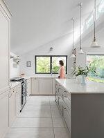Moderne Landhausküche mit hellgrauen Fronten und hoher Decke