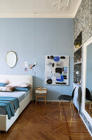 Pale blue wall in bedroom with stucco ceiling and herringbone parquet floor