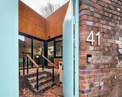 Blick durchs offene Hoftor auf modernes Haus mit rostiger Fassade