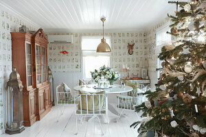 Decorated Christmas tree, round dining table and dresser in rustic interior