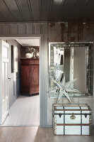 Old wooden trunk below mirror on wall and Christmas decoration in hallway
