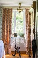 Runder Beistelltisch vor Fenster mit Vorhang und Kleiderschrank im Schlafzimmer