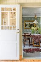 Blick ins Esszimmer mit Holztisch, Gemäld an Wand mit Tapete