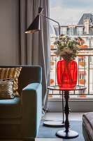 Red glass vase on side table and standard lamp next to French windows