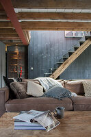 Rustic living room in shades of grey and brown with metal stairs on wooden beam