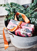 Verpacktes Geschenk in einer Blechwanne mit Nadelzweigen