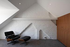 Designersessel vor weißer Backsteinwand unter der Dachschräge