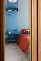 Blue cloakroom panel used as bedside table next to bed