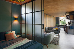 Frosted glass sliding door between bedroom and open-plan interior