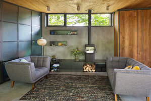 Pale grey sofas and log burner in open-plan interior