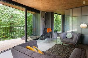 Grey sofa set in front of glass sliding door in open-plan interior