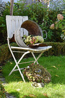 Wreath of hydrangeas in old zinc tub without base on chair