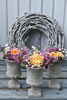 Summer bouquets of roses, Caucasian crosswort and gypsophila in small concrete urns in front of wreath of white-painted vines