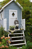 Planted bowl and dog on sheepskin rug, wreath on door knob and lantern outside small summer house