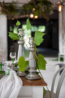 Silver candlesticks and tendrils of leaves on festively set table