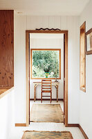 Blick durch geöffnetes Tür auf kleinen Schreibplatz vor Fenster mit Gartenblick