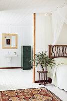 Blick auf Bett mit DIY-Betthaupt aus gesammelten Ästen und Bad Ensuite