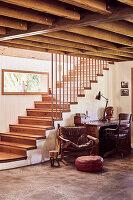 Holztreppe, Treppengeländer aus recycelten Kupferrohren, alter Ledersessel und Schreibtisch